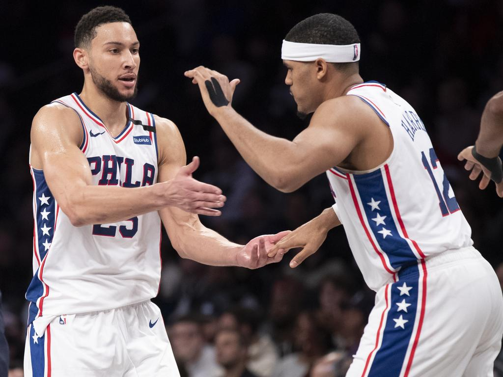 Ben Simmons celebrates with Tobias Harris as he comes to the bench during a timeout.