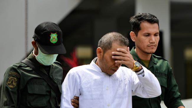 Aceh Ulema Council member Mukhlis is escorted by members of the sharia police before being whipped in public in Banda Aceh. Picture: AFP