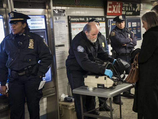 Members of the Transportation Security Administration and New York City Police Department check the bags of passengers as they enter the Times Square subway station during the evening rush hour. Picture: Getty