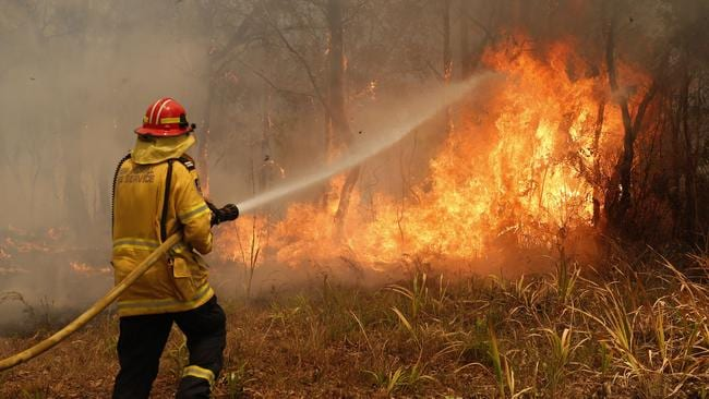 Firefighters work to contain a bushfire in Old Bar, NSW on Saturday. Picture: Darren Pateman/AAP