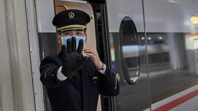 A train controller, wearing a face mask, gestures on a train platform at Beijing West Railway Station in Beijing on January 24, 2020. Picture: Nicolas Asfouri/AFP