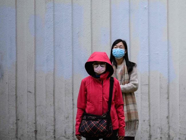 Pedestrians wear face masks as they prepare to cross a road in Hong Kong, which became the second place outside mainland China to report a death from the disease. Picture: Anthony Wallace / AFP.