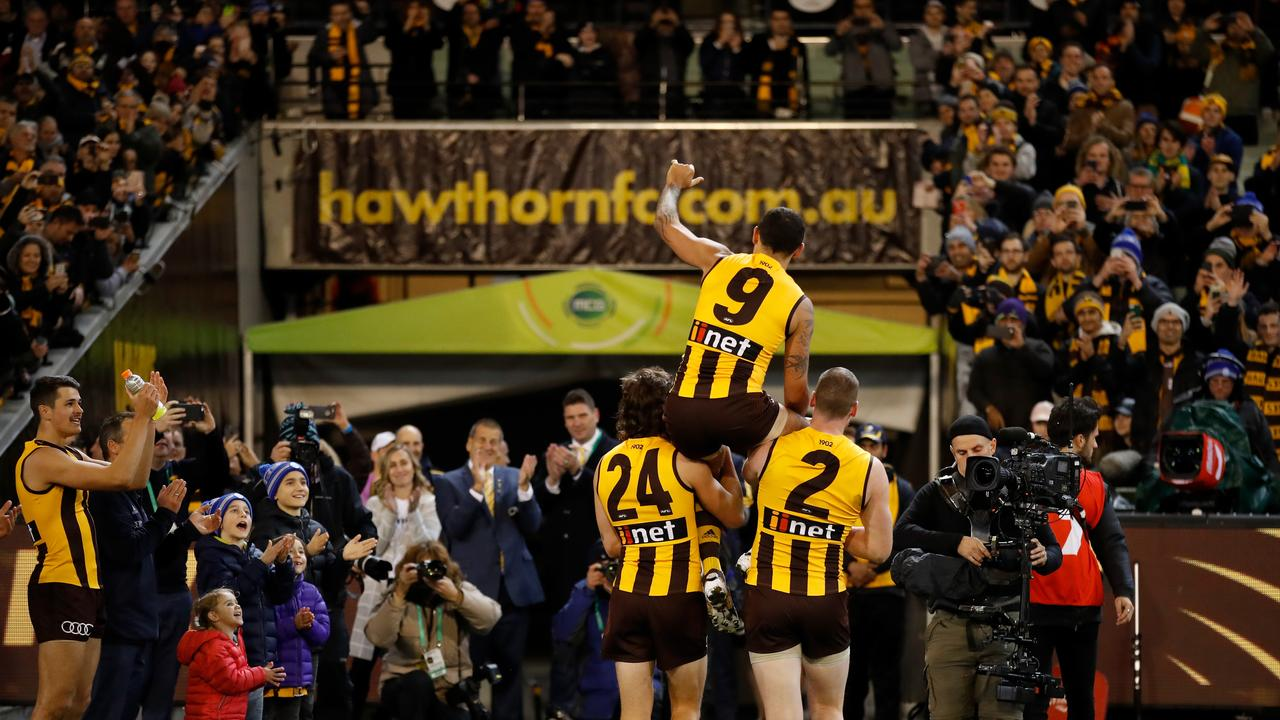 Shaun Burgoyne is carried off by Ben Stratton and Jarryd Roughead in his 350th.
