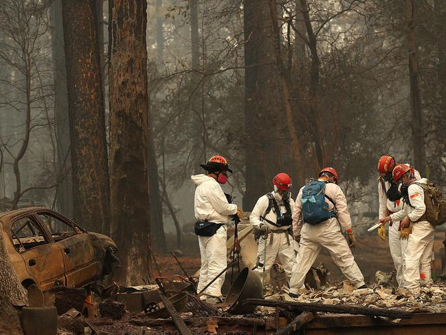 Rescue workers search for human remains at a home that was burned by the Camp Fire. Picture: Getty