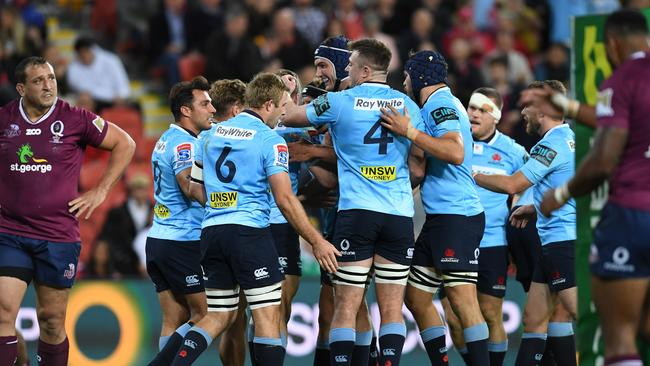 Waratahs players celebrate a try during their win over the Reds at Suncorp Stadium.