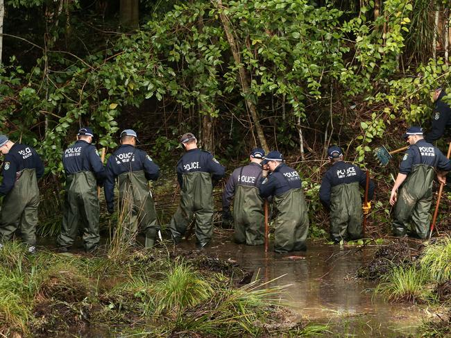 Police wade through a creek looking for any trace of the missing toddler. Picture: Peter Lorimer