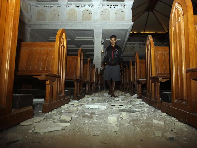 A man walks inside a cathedral where debris has fallen after an earthquake struck Bali. Picture: AP.