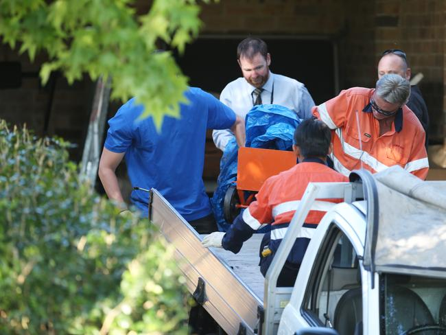 BOC Gases employees help police remove two gas cylinders from the home. Picture Craig Greenhill