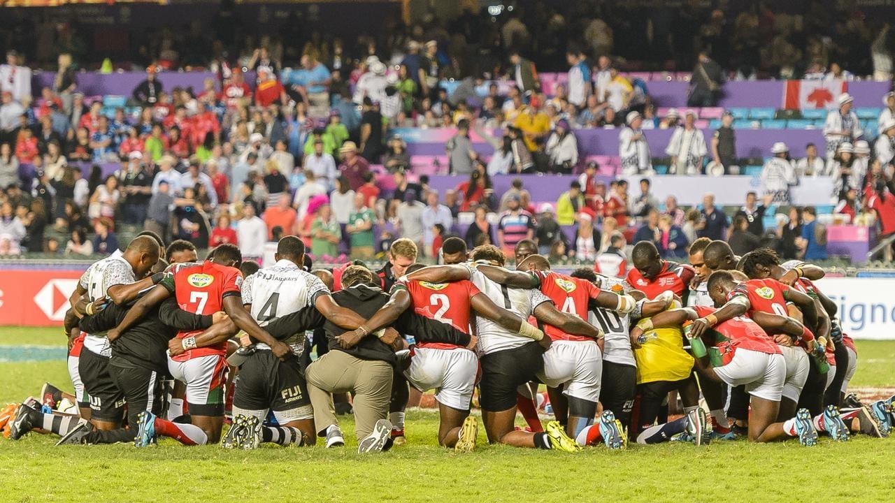 The Fiji and Kenya sevens teams pray together after the final in Hong Kong.