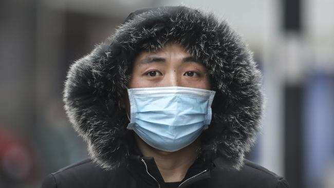 A man wears a mask while walking in the street in Wuhan, Hubei province, China. Picture: Getty Images