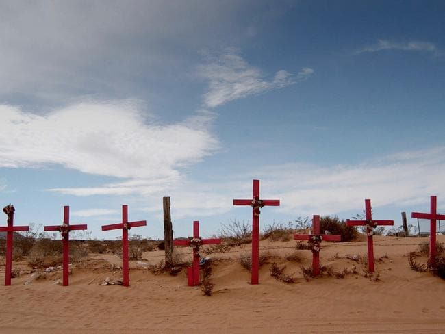 Pink crosses mark the desert graves of young women murdered in the border town of Juarez, Mexico.