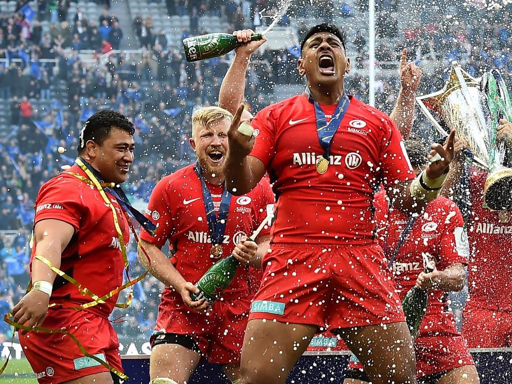 The champagne is sprayed as Saracens' players including Saracens' New Zealand born Australian lock Will Skelton (C) celebrate their win on the field after the European Rugby Champions Cup final match between Leinster and Saracens at St James Park stadium in Newcastle-upon-Tyne, north east England on May 11, 2019. - Saracens won a third European Champions Cup title in four years with a 20-10 win over Leinster on Saturday. (Photo by Glyn KIRK / AFP)
