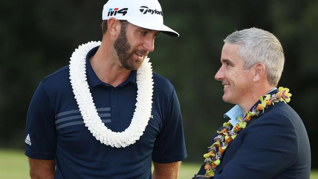 Dustin Johnson of the United States speaks to PGA commissioner Jay Monahan after winning the Tournament of Champions.