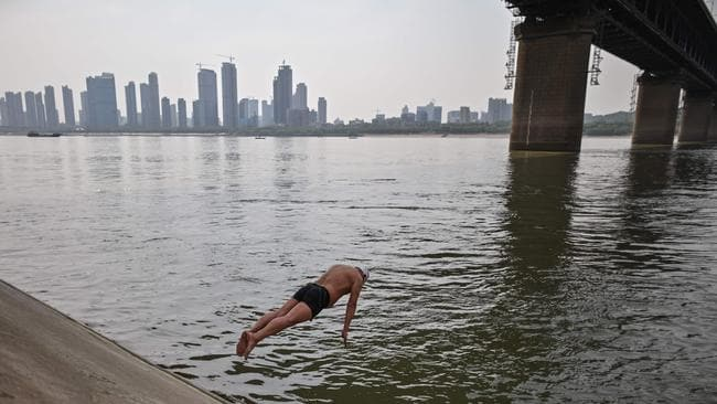 A man jumps into the Yangtze river in Wuhan, China's central Hubei province on April 16. China says it has largely brought the coronavirus under control within its borders.