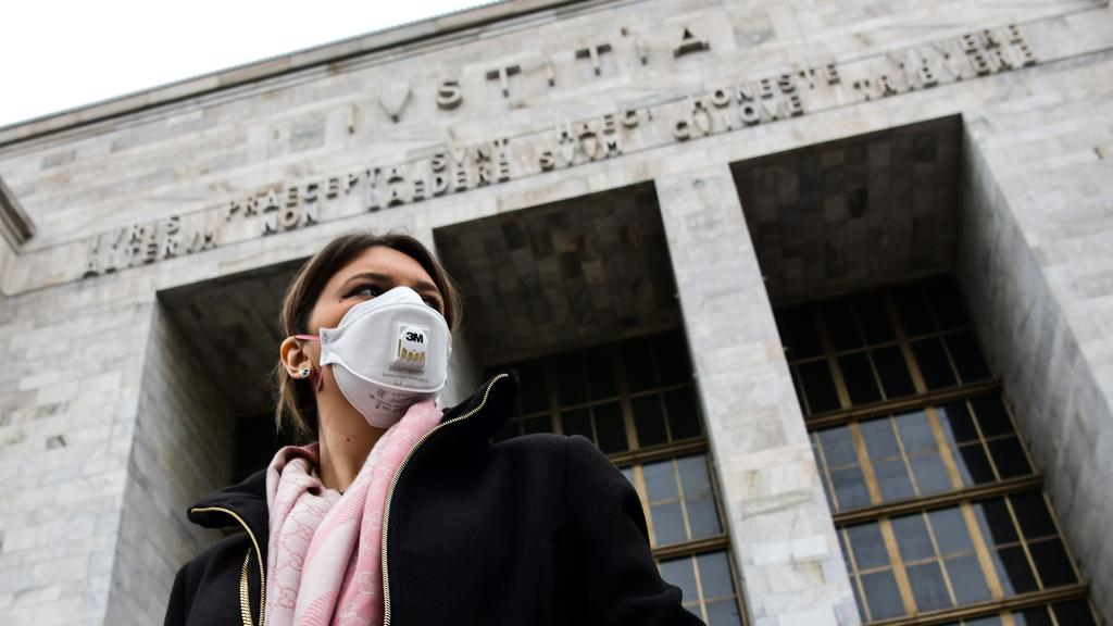 A woman wearing a respiratory mask exits from the Palace of Justice in Milan.