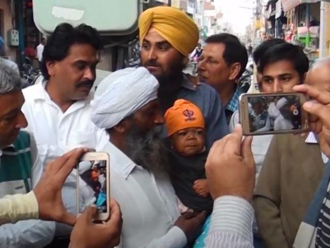 好奇心local盛な地元の人々が写真を撮るので、赤ちゃんの体に閉じ込められた23歳の男性、マンプリート・シンは親relativeによって運ばれます。 写真:YouTube