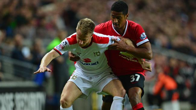 MK Dons midfielder Dean Bowditch vies with Manchester United's youngster Saidy Janko.