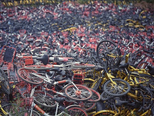 Bicycles of Chinese bike-sharing services Mobike (orange) and ofo (yellow) are piled up in an abandoned brick factory in Wangzuo town, Fengtai district, Beijing, China, 6 June 2018. Picture: AFP