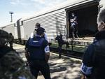 """Monitors from the Organization for Security and Cooperation in Europe (OSCE) and members of a forensic team inspect a refrigerator wagon containing the remains of victims from the downed Malaysia Airlines Flight MH17, at a railway station in the eastern Ukrainian town of Torez on July 21, 2014. The head of a Dutch forensic team said on Monday a train, carrying the remains of victims from the Malaysian airliner crash, should set off later on Monday to a place where """"we can do our work"""" AFP PHOTO/ BULENT KILIC"""
