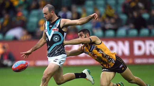 Matthew Broadbent of the Power gets a kick away ahead of Hawthorn's Paul Puopolo. Picture: AAP Image/Julian Smith