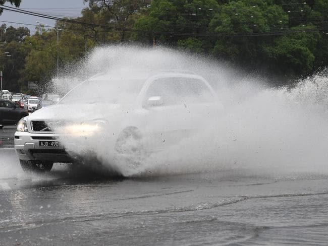 Cars are seen passing through the water covered intersection of Racecourse road and Flemington road in Melbourne. Picture: AAP Image/James Ross