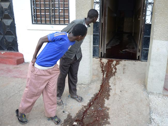Cold-blooded murder ... men look at a pool of blood at the entrance of a Mpeketoni restaurant where people tried to hide, but were shot.