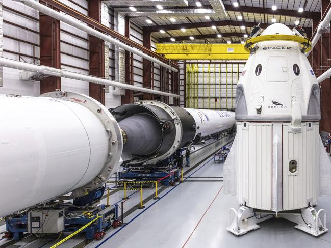 SpaceX's Crew Dragon spacecraft and Falcon 9 rocket are positioned inside the company's hangar. Picture: AP