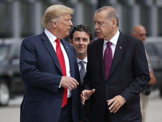 Donald Trump walks and chats with Turkish president Recep Tayyip Erdogan as they arrive together for a 'family photo' at the NATO summit. Picture: AP