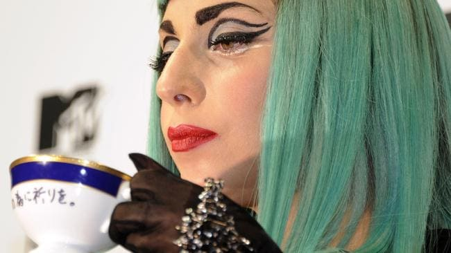 Lady Gaga drinking tea with a 'Pray for Japan' engraved cup during a press conference.