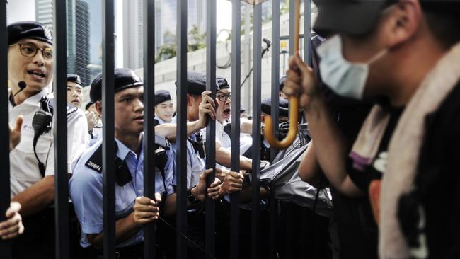 Police officers hold on to the gate as they block and argue with protesters who have surrounded the police headquarters in Hong Kong. Picture: AP