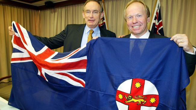 In 2003, then NSW premier Bob Carr presents the NSW flag to the Queensland Premier Peter Beattie after the State of Origin series loss. Picture: Bruce Long.