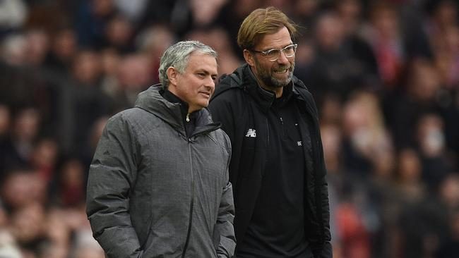 Manchester United's Portuguese manager Jose Mourinho (L) talks with Liverpool's German manager Jurgen Klopp (R)