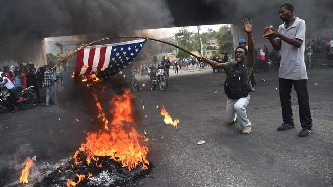 A protester burns a US flag during a demonstration in the Haitian Capital Port-au-Prince. Picture: Hector Retamal