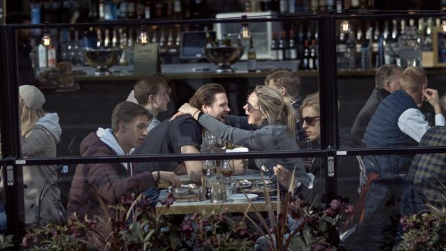 A couple hug and laugh as they have lunch in a restaurant in Stockholm, Sweden.