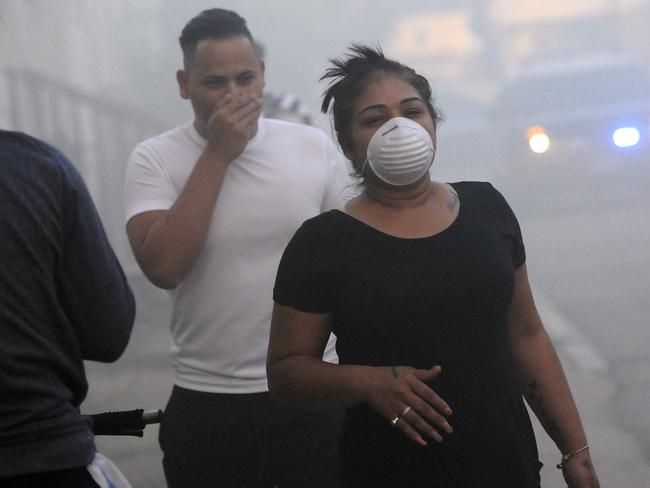 Residents cover their face from the smoke while being evacuated from homes as firefighters battle a fire on Bowdoin St., Thursday, Sept. 13, 2018 in Lawrence. Picture: Tim Jean