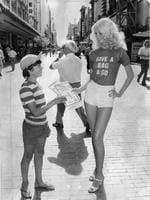 Model Debbie Mead, 16, hands 12-year-old David Buhagiar a KESAB rubbish bag in a campaign to pick up litter in 1977.