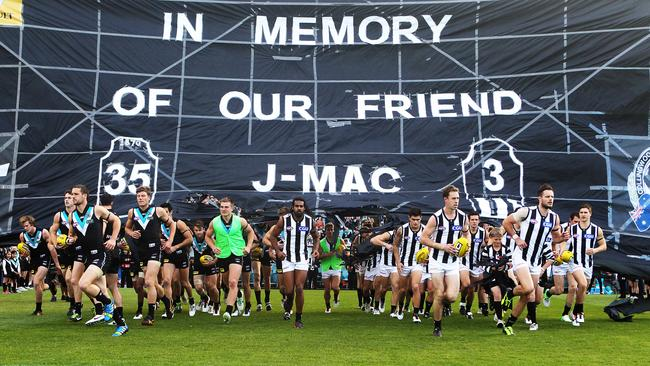 AFL teams Port Adelaide and Collingwood run through a banner commemorating player John McCarthy, who died on this day in 2012.