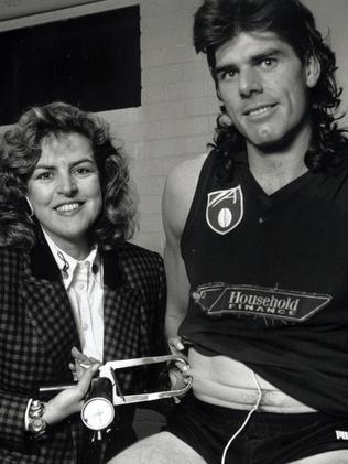 Hawks legend Gary Ayres being given a pinch test by dietitian Karen Inge.