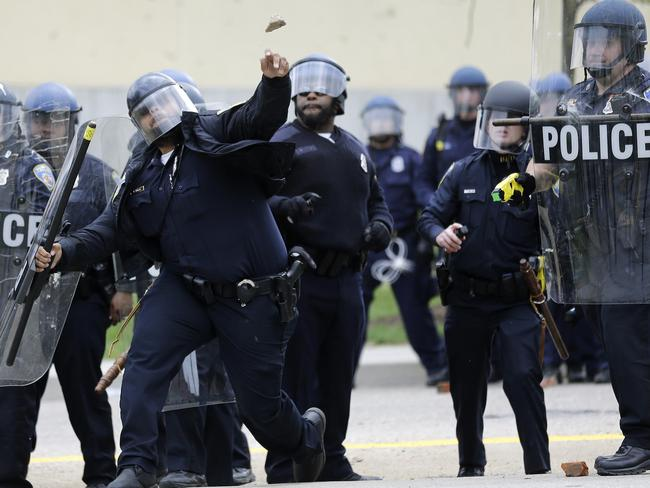 Ugly clashes ... A police officer throws an object at protesters to try and keep them at bay. Picture: AP/Patrick Semansky