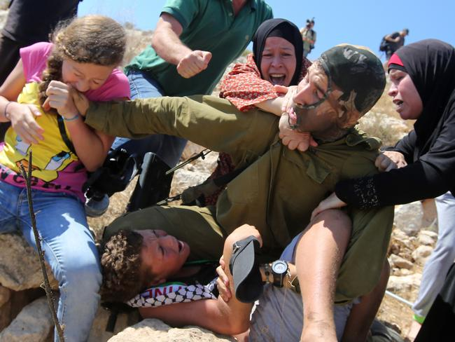 Three members of the Tamimi family fight with an Israeli soldier in Palestine. Picture: Abbas Momani/AFP