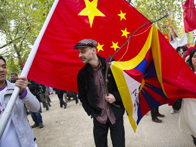A man with a Tibet flag is swamped by pro-China protesters during the start of the four-day official visit. Picture: AFP/JACK TAYLOR