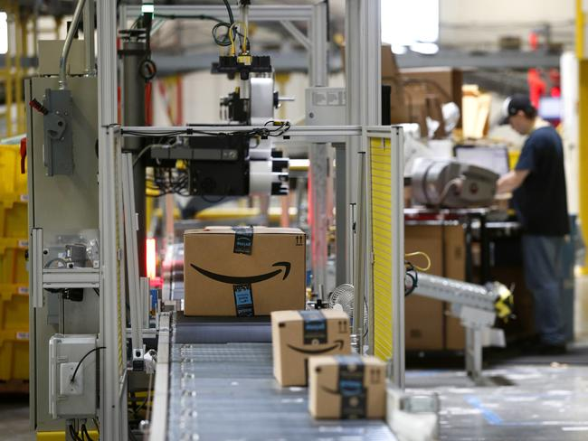 "Packages pass through a scanner at an Amazon ""fulfilment centre"" in Baltimore. Amazon is paying workers to defend the company on Twitter, reassuring critics that they make enough money to live and are allowed to take bathroom breaks. Picture: Patrick Semansky"