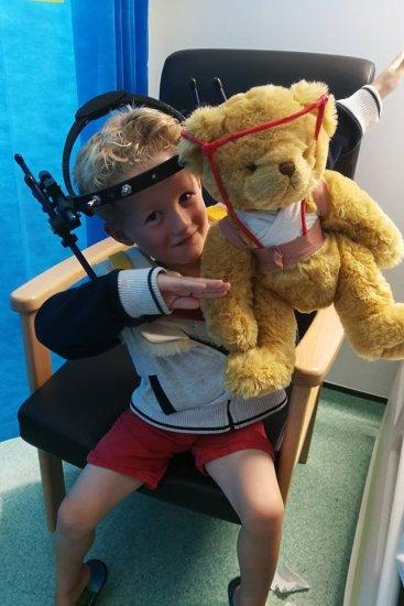 Riley Hoy from Clevedon, North Somerset, had his teddy bear called Jamie also fitted with a metal halo brace after he needed one when he broke his neck. See SWNS story SWNECK; A five-year-old boy broke his neck doing a backflip on a trampoline - but bravely faced his long recovery with the help of a teddy with a matching metal brace. Brave Riley Hoy spent two months in a frame which was bolted to his skull after the he landed on his neck in his garden. Doctors initially failed to notice he had broken his neck for five weeks - and he even went swimming and camping before a scan revealed the break. He was fitted with a 'halo' neck brace for eight weeks, and a neighbour gave him a teddy with a matching structure - made from straws and tape - to help him through. And after seeing how much 'Jamie Bear' helped Riley, a family friend made a whole family of similar teddies with neck and leg braces to help other children.