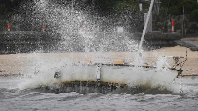 Waves smash a sailing boat on St Kilda Beach. Picture: David Caird