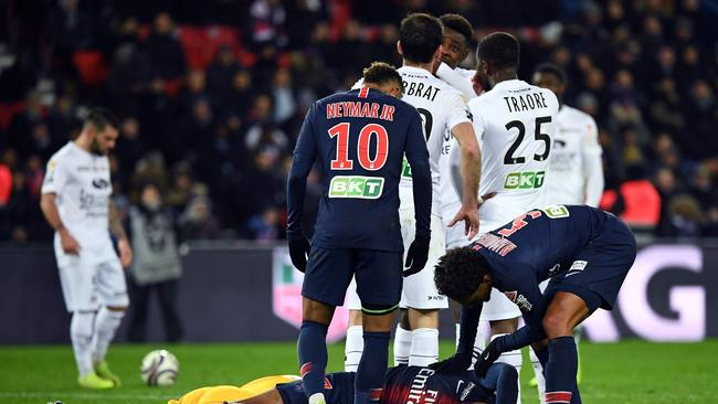 Paris Saint-Germain's French forward Kylian Mbappe (down) lies on the ground after a collision