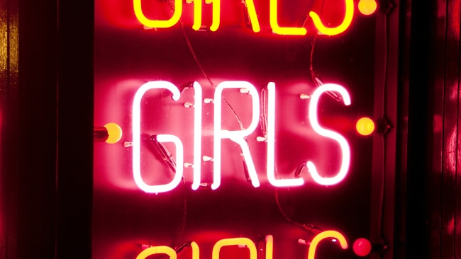 A glowing red neon striptease sign on a building at night. Photo: iStock