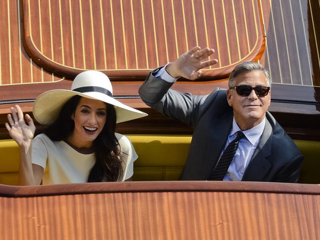 In love ... George Clooney, right, and Amal Alamuddin wave from a boat as they leave after a civil weeding ceremony at the town hall in Venice, Italy. Picture: AP
