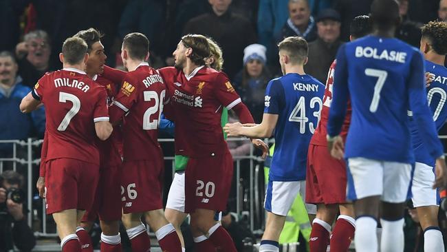 Liverpool's Brazilian midfielder Roberto Firmino (L) is restrained by teammates