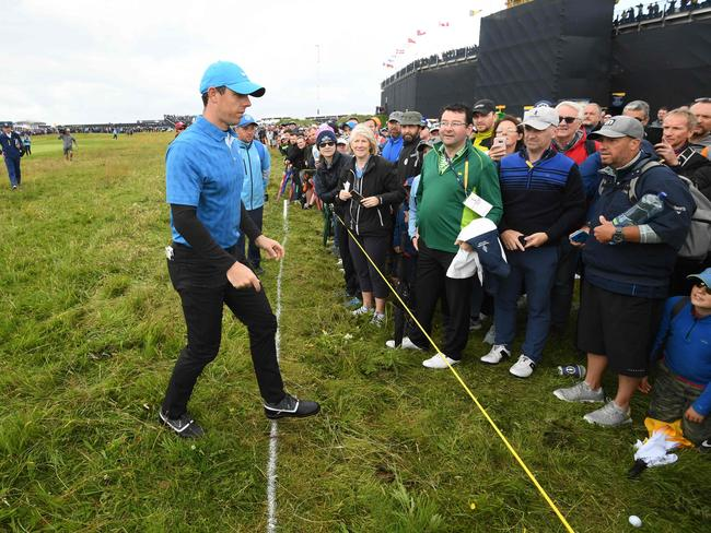 Rory McIlroy retrieves his ball on the first hole. (Photo by Glyn KIRK / AFP)