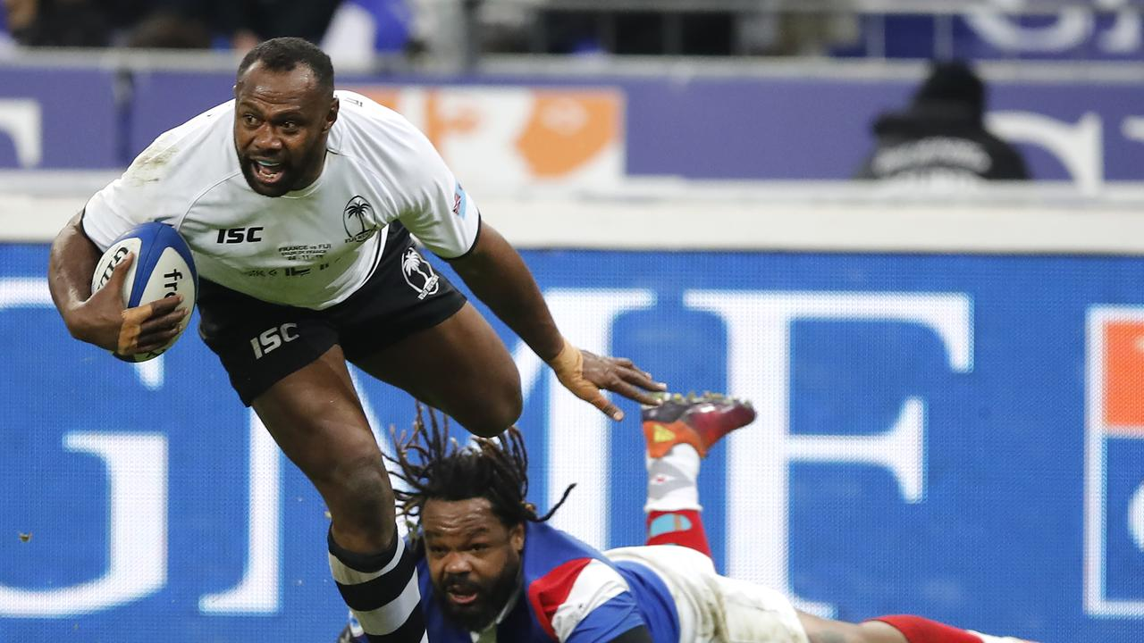 Fiji's Vereniki Goneva evades the tackle of France's Mathieu Bastareaud as he scores a try.